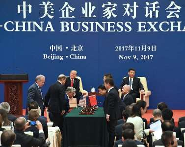 Officials from West Virginia (left side of the table) and China Energy sign the MOU. Credit: WV Dept. of Commerce