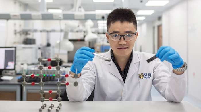 NUS PhD student Mr. Liu Wei showing the 2-D graphene-like polymer (left), and a piece of carbon paper coated with the material (right). Source: National University of Singapore
