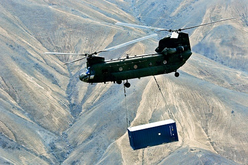 A CH-47 transports a shipping container using a sling. ISO containers are not designed for sling lifting, but some suppliers weld padeyes to their corners for this purpose, increasing the risk of collapse.