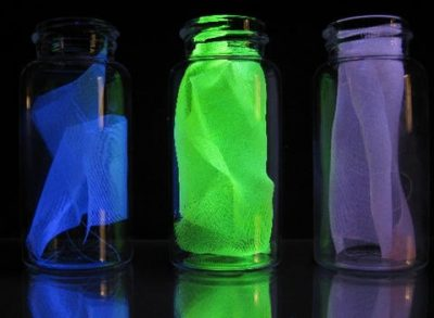 Examples of the silk used in experiments to detect damage in composites, shown under black light. (Left) Ordinary fibroin of the Bombyx mori silk worm. The observed fluorescence is the result of molecules already present in the protein structure of the fiber. (Middle) Mechanophore-labeled silk fiber fluoresces in response to damage or stress. (Right) Control sample without the mechanophore. Source: Chelsea Davis and Jeremiah Woodcock/NIST