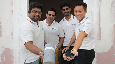 The researchers display enhanced concrete (left) and a sample of biochar generated from wood waste (right). Source: NUS