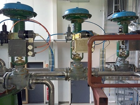 These control valves feature valve positioners that can compare measurements and apply corrections. Source: Bitjungle/CC BY-SA 4.0, from Wikimedia Commons.
