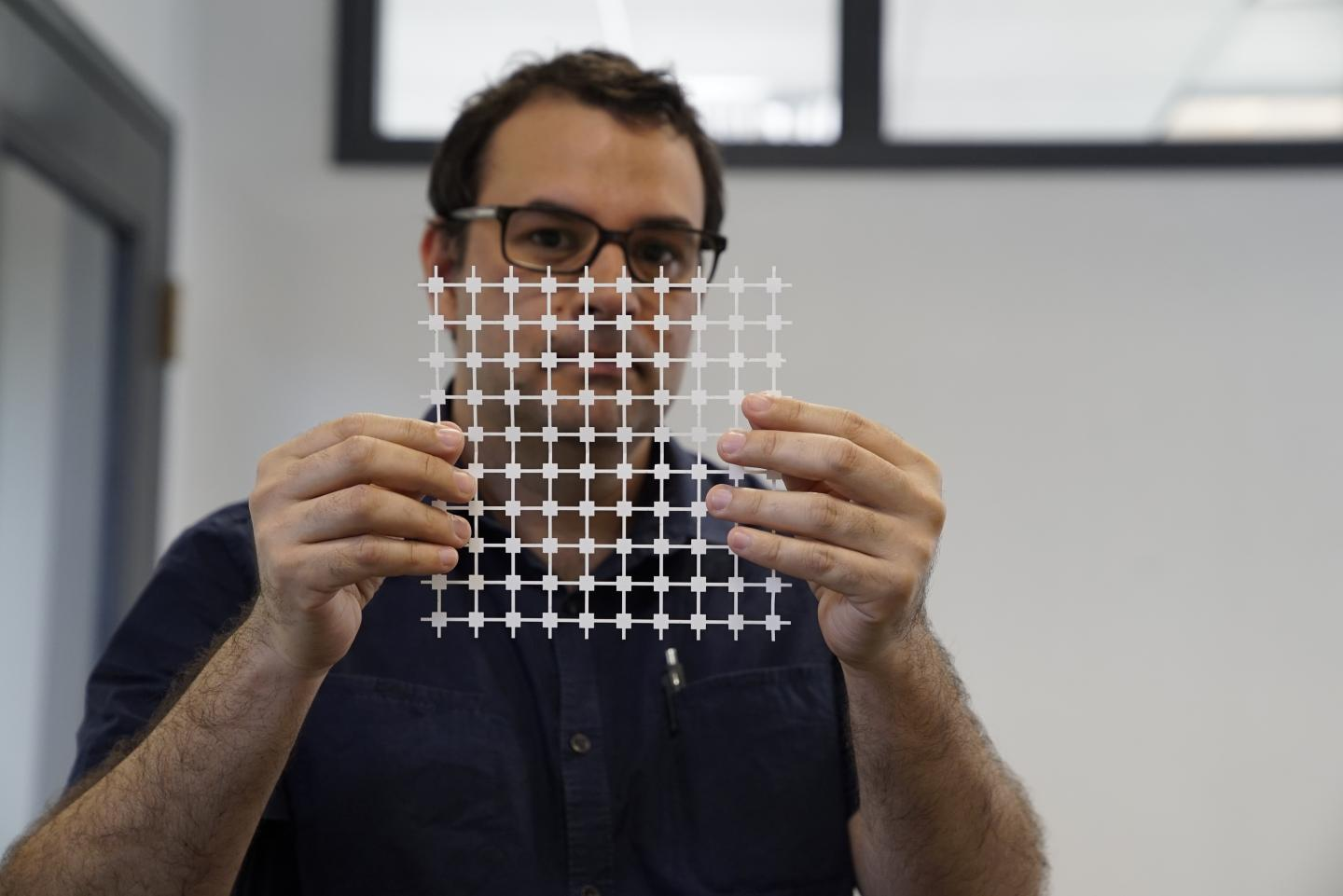 Jose Gomez-Marquez, co-director of MIT's Little Devices Lab, holds a sheet of paper diagnostic blocks, which can be easily printed and then combined in various ways to create customized diagnostic devices. (Source: Melanie Gonick/MIT)
